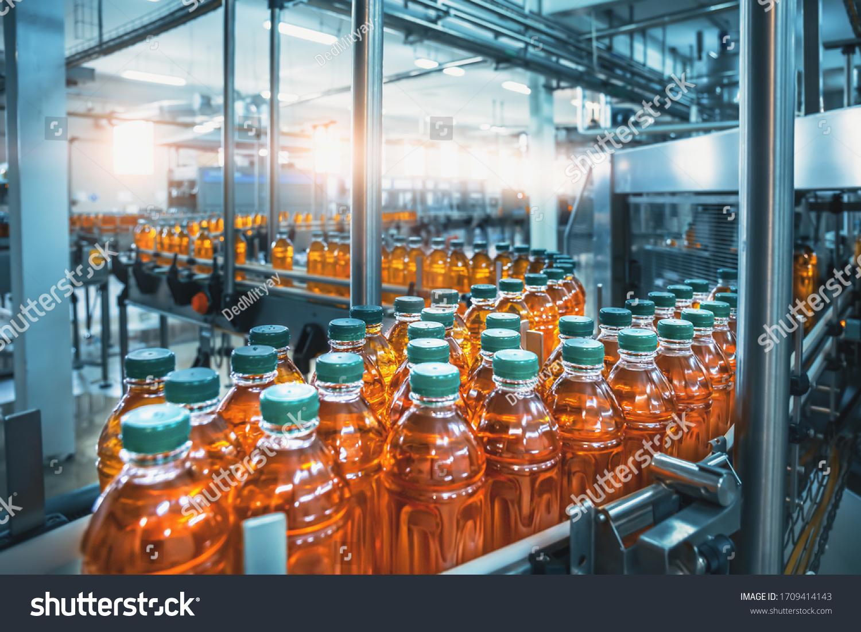 Conveyor belt, juice in bottles, beverage factory interior in blue color, industrial production line. #1709414143