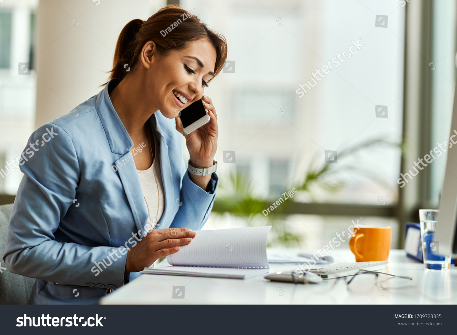 Happy businesswoman talking on mobile phone while analyzing weekly schedule in her notebook. #1709723335