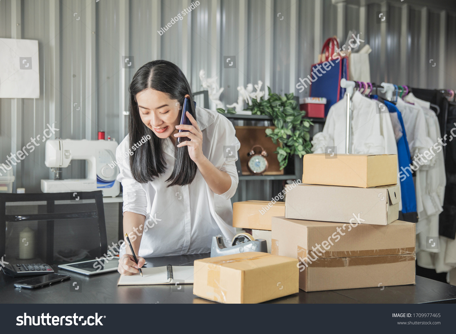Young business woman working online e-commerce shopping at her shop. Young woman seller prepare parcel box of product for deliver to customer. Online selling, e-commerce. #1709977465