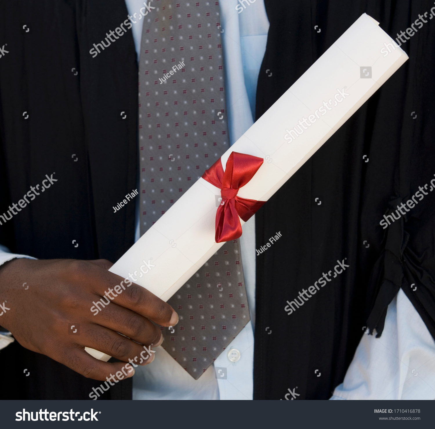 Close-up of a graduate holding a diploma #1710416878