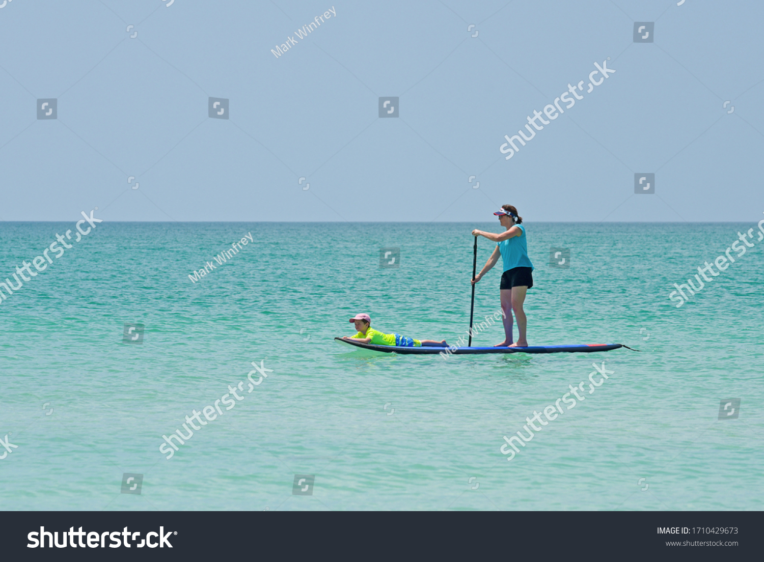 HOLMES BEACH, ANNA MARIA ISLAND, FL - APRIL 30, 2018: A Mom and her Young Son on a Paddleboard in the shallow water of the Gulf of Mexico enjoying a Beautiful Summer Day.