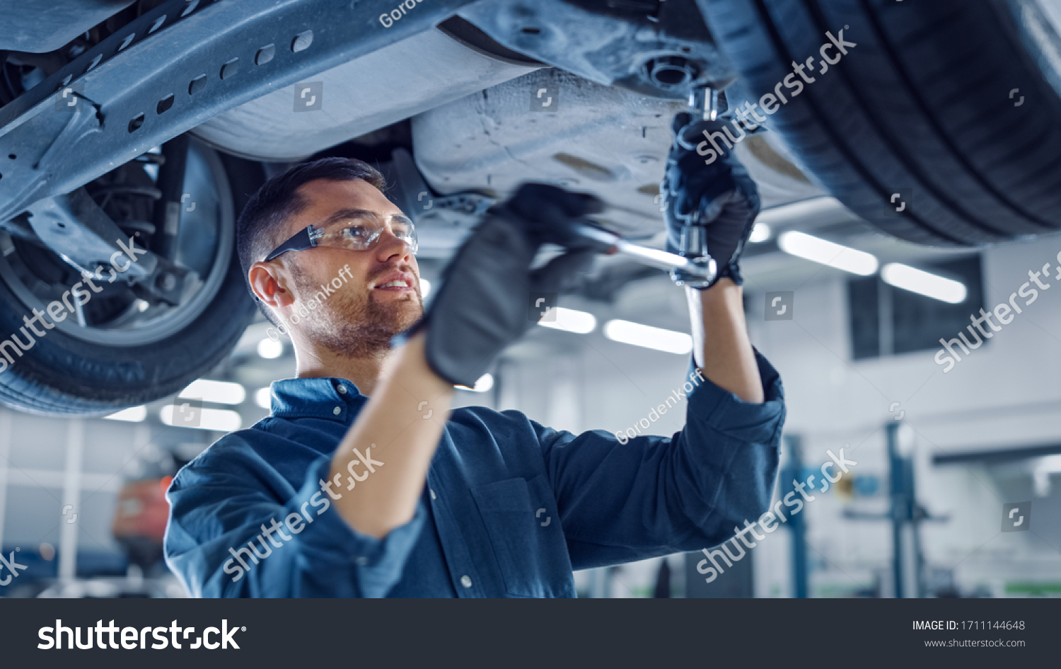 Portrait Shot of a Handsome Mechanic Working on a Vehicle in a Car Service. Professional Repairman is Wearing Gloves and Using a Ratchet Underneath the Car. Modern Clean Workshop. #1711144648