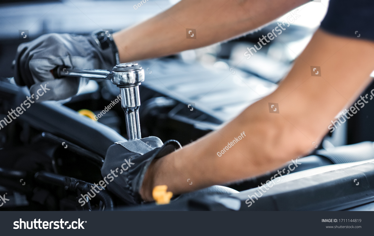 Close Up Shot of a Professional Mechanic Working on Vehicle in Car Service. Engine Specialist Fixing Motor. Repairman is Wearing Gloves and Using a Ratchet. Modern Clean Workshop. #1711144819