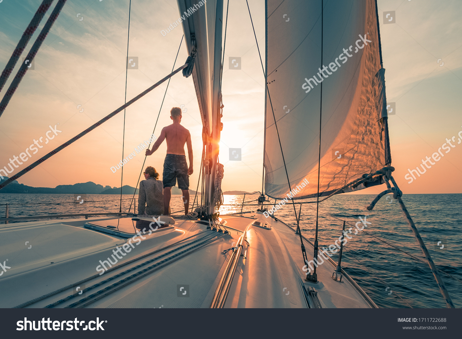 Young couple sailing on the boat at sunset #1711722688