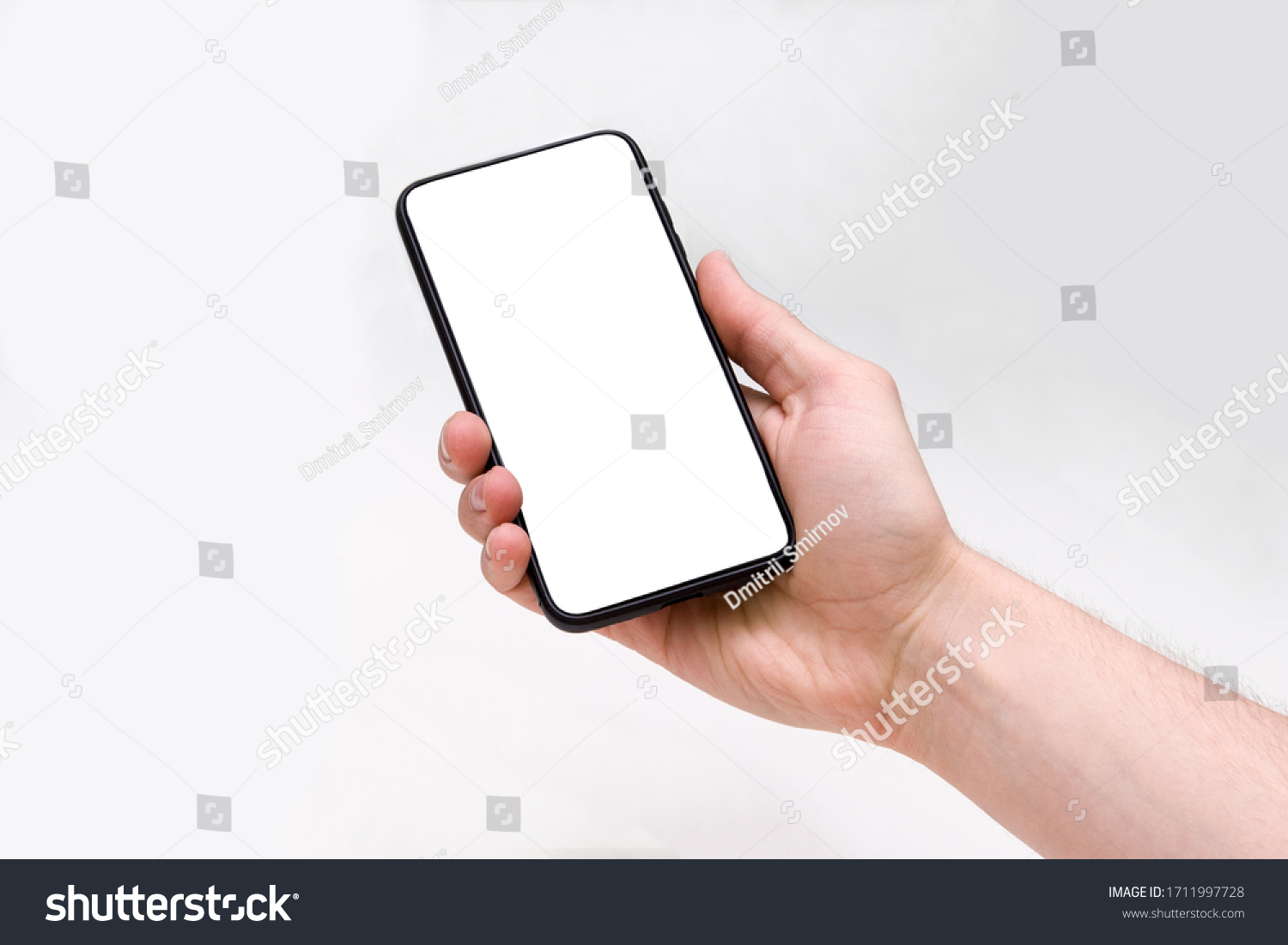 Man holding smartphone with blank screen on white background, closeup of hand. Space for text #1711997728