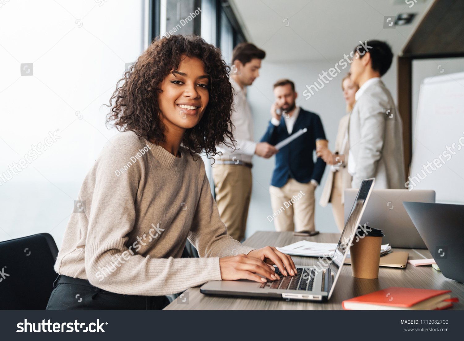 Attractive african young confident businesswoman sitting at the office table with group of colleagues in the background, working on laptop computer #1712082700