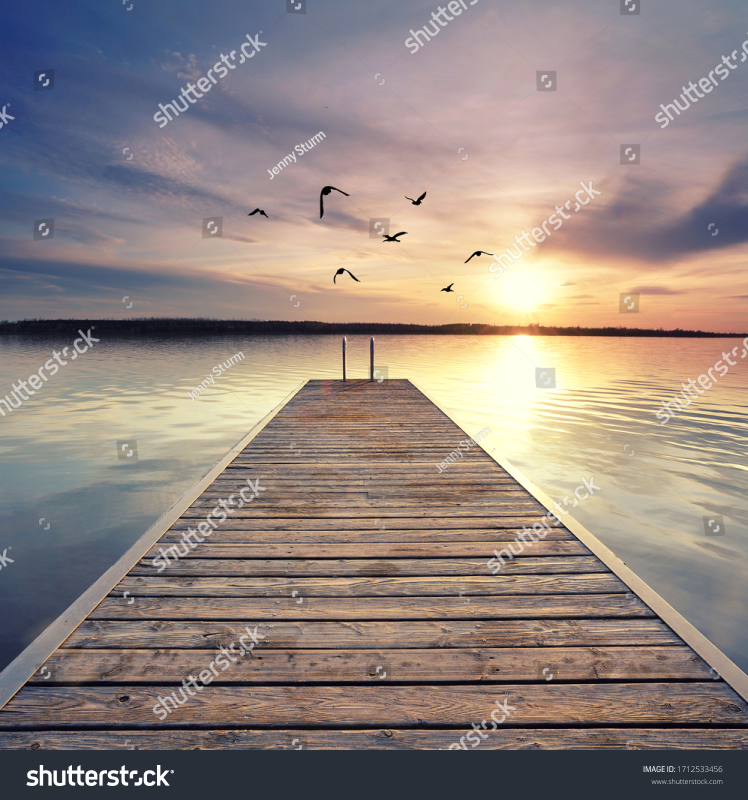 beautiful sunset at the wooden jetty at the beach #1712533456
