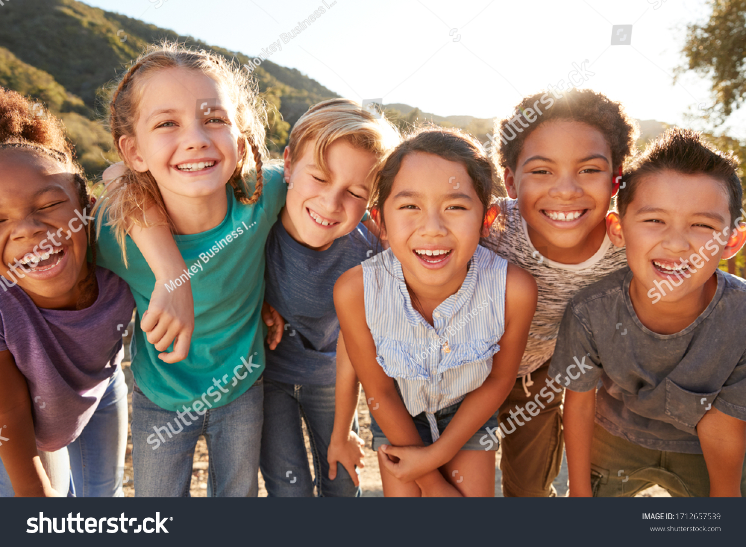 Portrait Of Multi-Cultural Children Hanging Out With Friends In Countryside Together