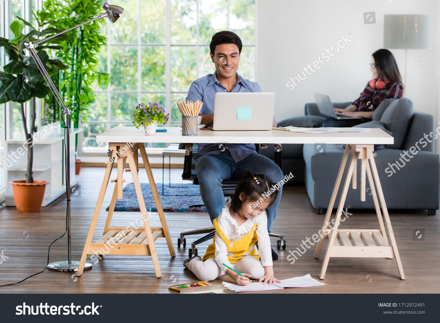 Mixed race family sharing time in living room. Caucasian father using notebook computer to work and half-Thai playing and painting under desk while Asian mother with laptop working her job on sofa. #1712972491