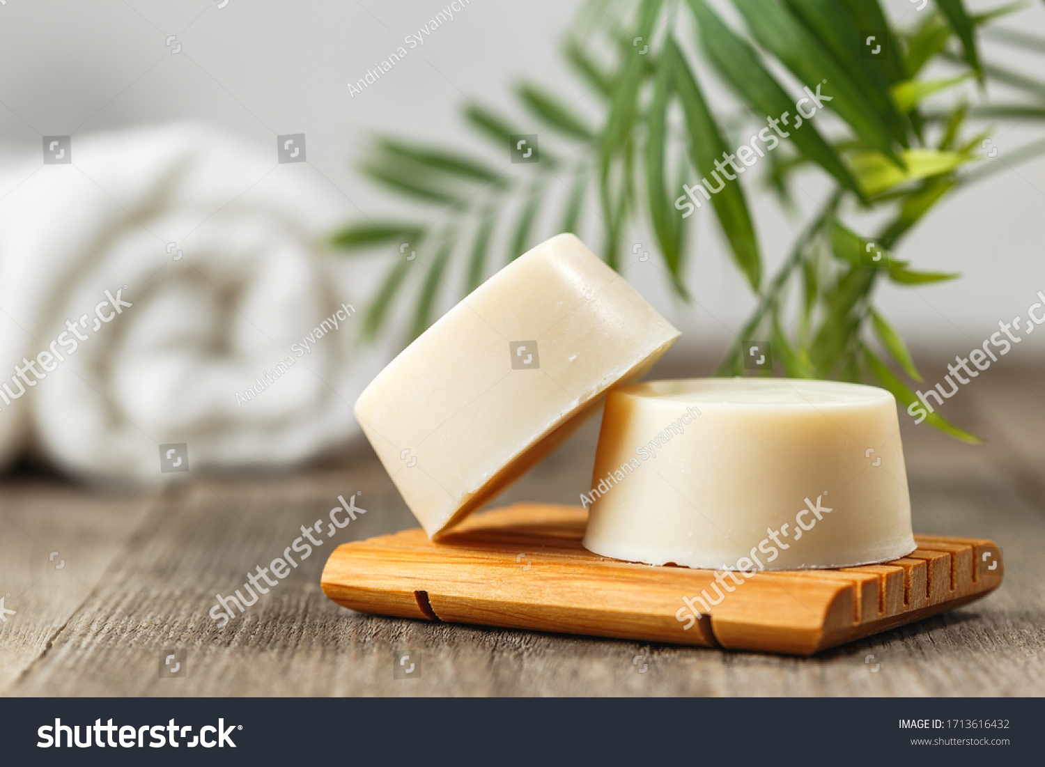 Handmade solid shampoo soap bar on wooden dish. Green leaves above and towel on the background. Zero waste, eco friendly product #1713616432
