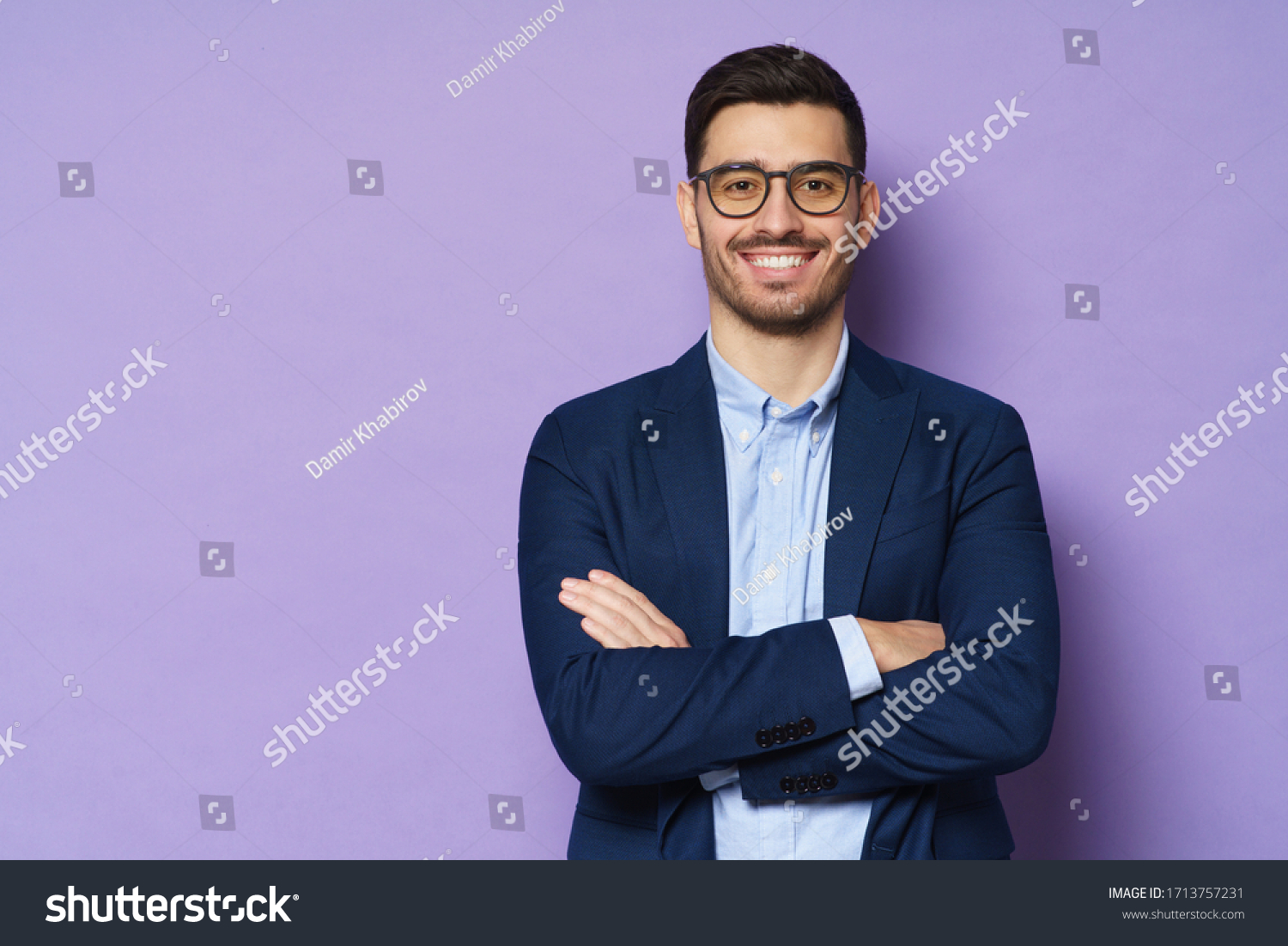 Young buisnessman wearing eyeglasses, jacket and shirt, holding arms crossed, looking at camera with happy confident smile, standing against purple background #1713757231