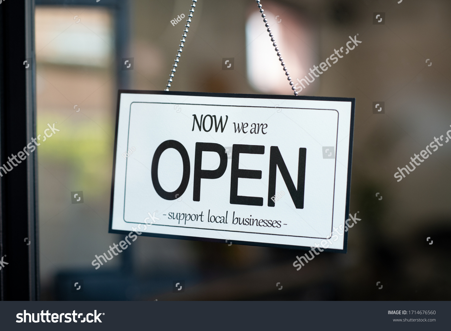 Reopening of a small business activity after the covid-19 emergency, ended the lockdown and quarantine. A business sign that says now we are open support local businesses hang on door at entrance. #1714676560