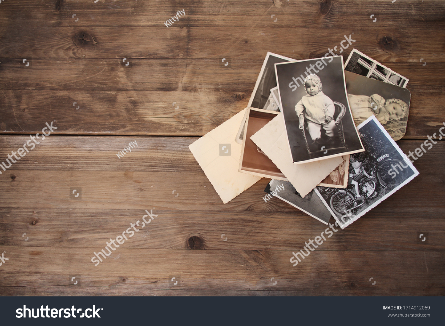 old vintage monochrome photographs, pictures taken in 1968, in sepia color are scattered on a wooden table, concept of genealogy, the memory of ancestors, family ties, memories of childhood #1714912069