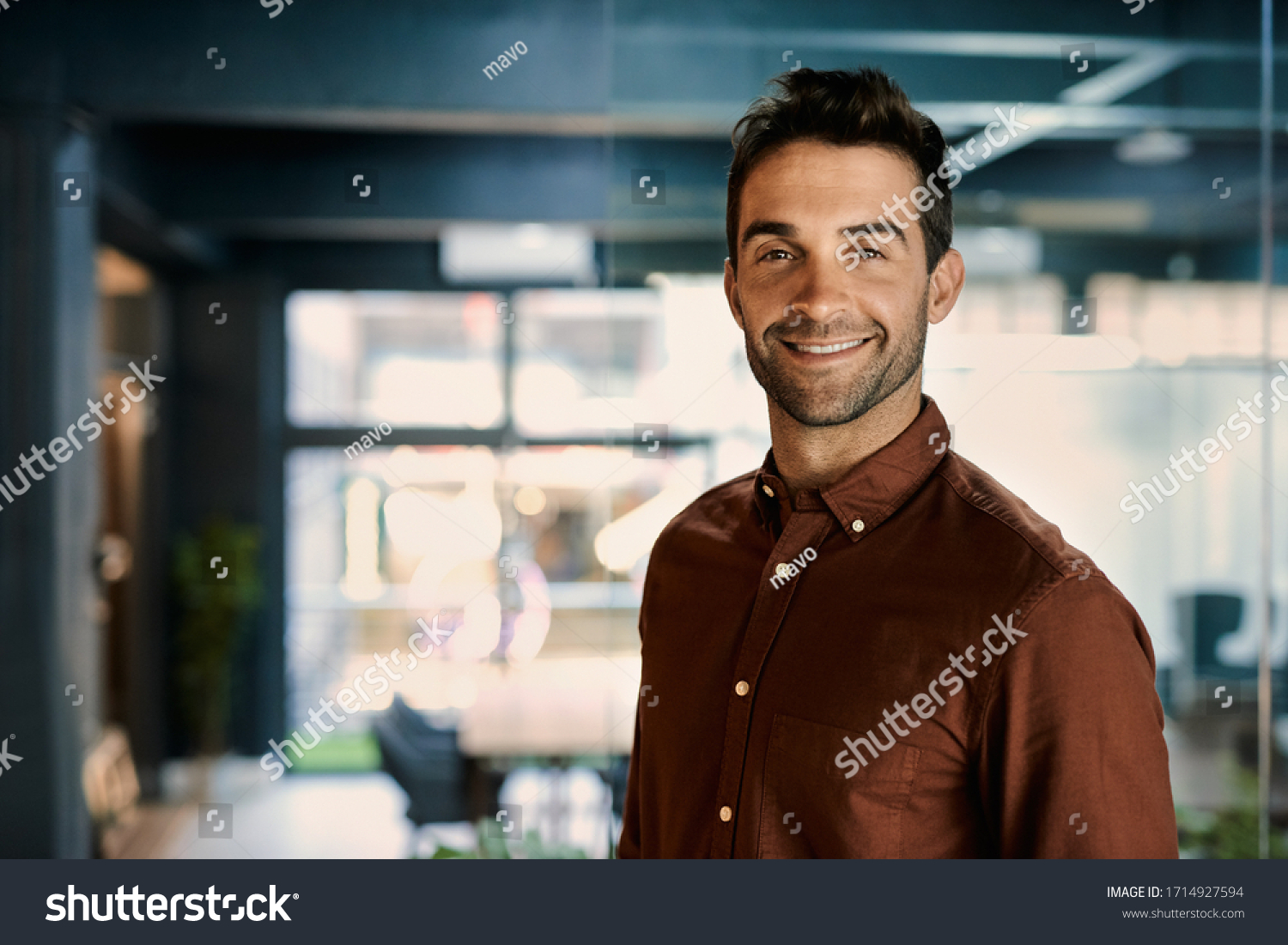 Portrait of a smiling young businessman standing alone in a dark office while working late #1714927594