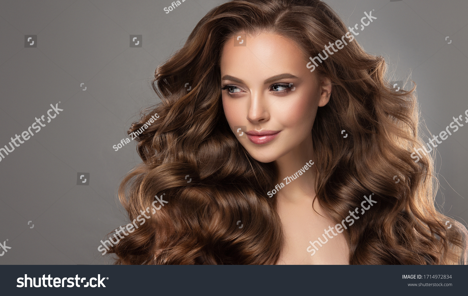 Beautiful model girl with long wavy and shiny hair . Brunette woman with curly hairstyle #1714972834