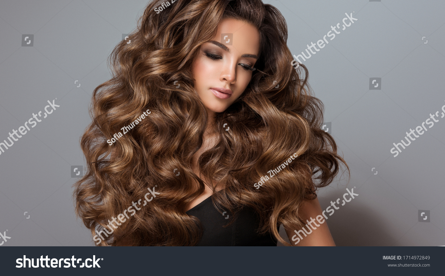Beautiful model girl with long wavy and shiny hair . Brunette woman with curly hairstyle  #1714972849