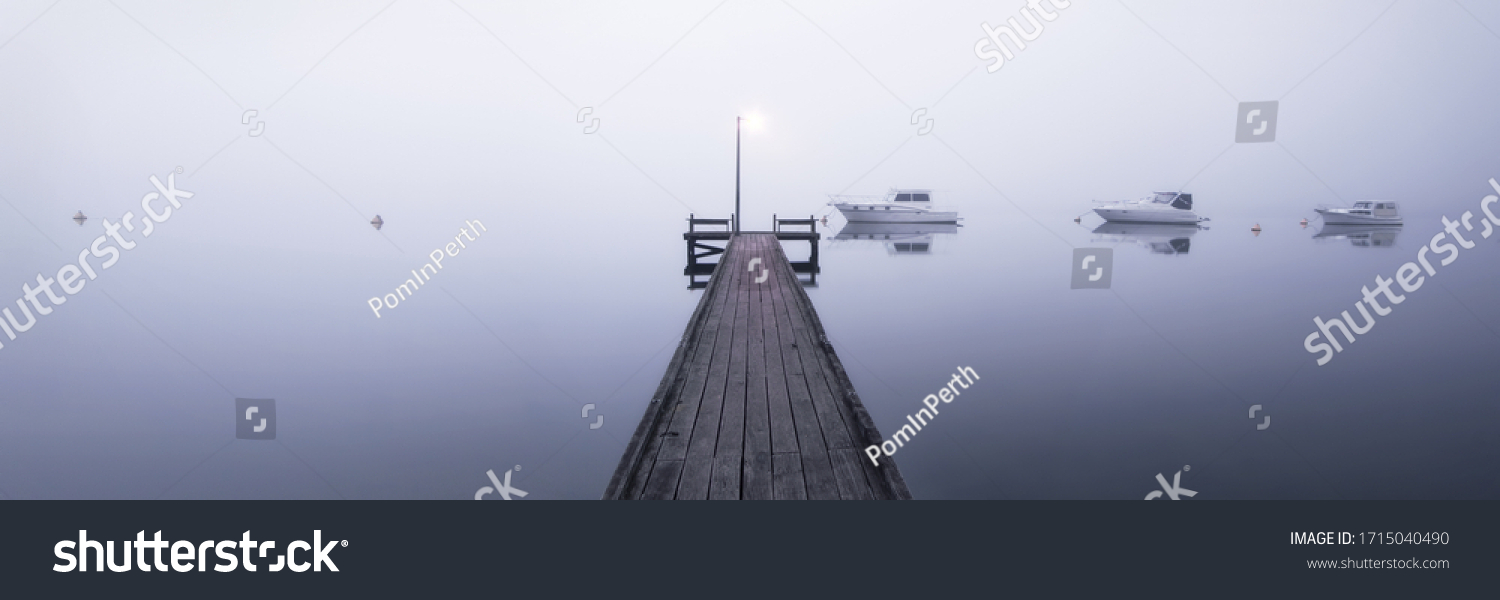 A jetty on a foggy morning with boats moored