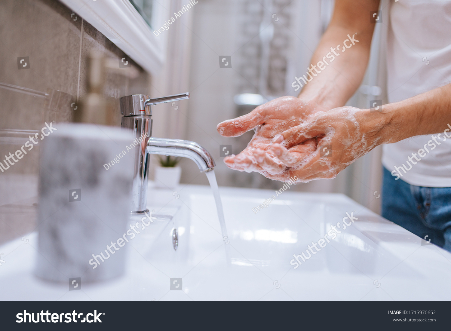 Close up of caucasian man washes his hands in the bathroom. COVID - 19 prevention #1715970652