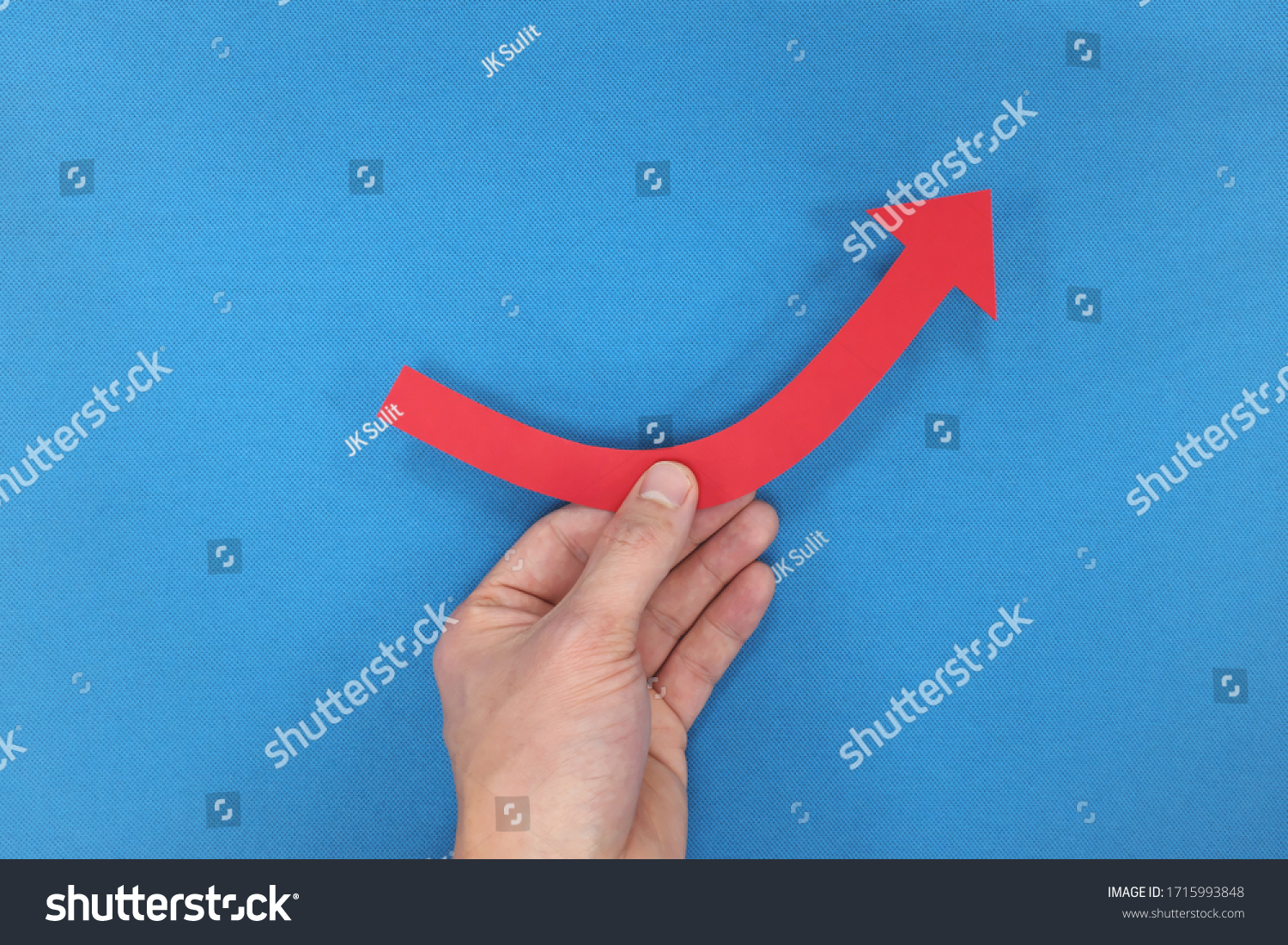 Male hand holding a red arrow graph going upward in blue background. Business recovery, growth, bounce back concept. #1715993848
