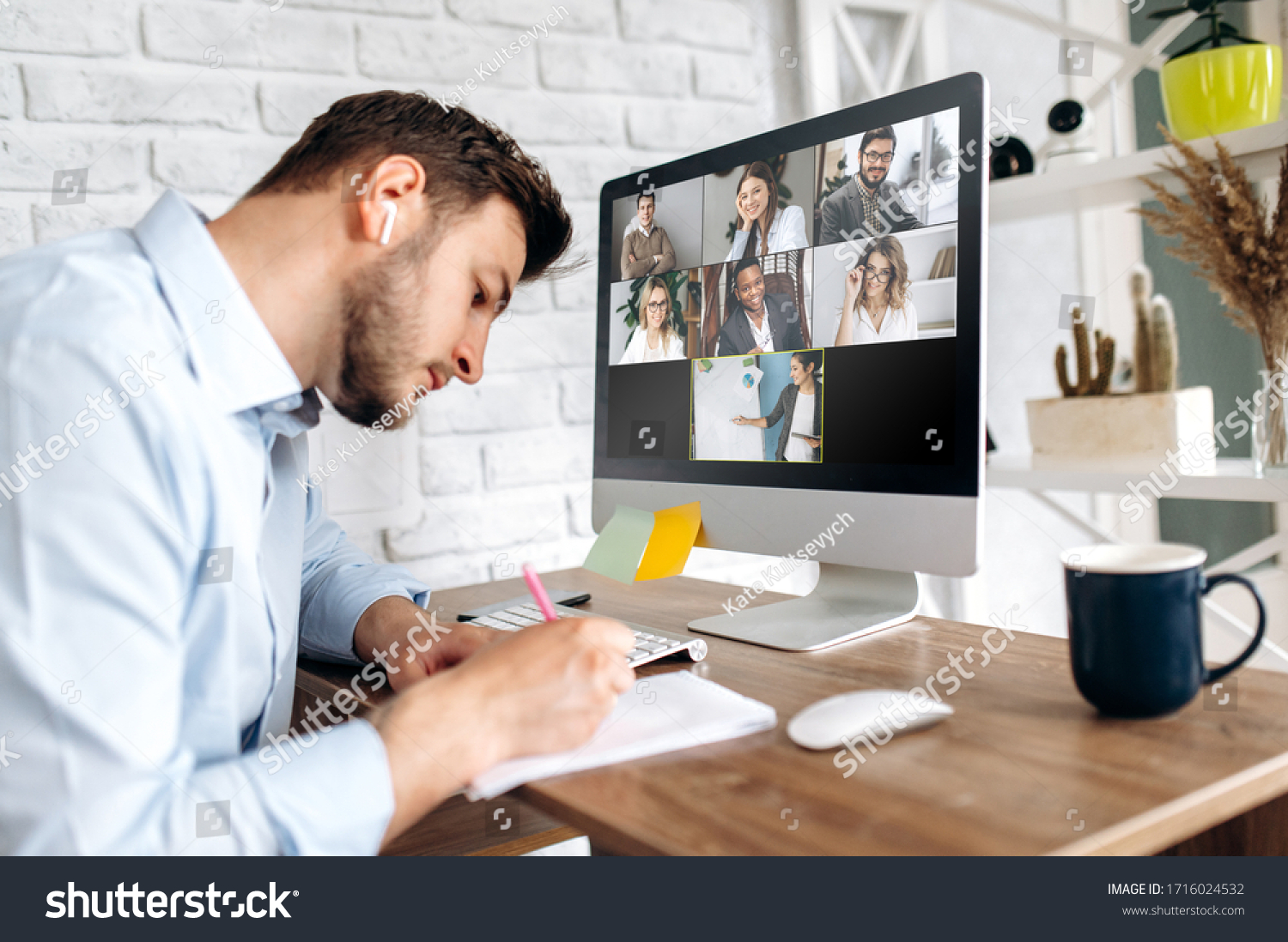 Online training. Young guy learns online by video conference in zoom app. On the screen, the teacher tells the information to him and other participants in the conference #1716024532