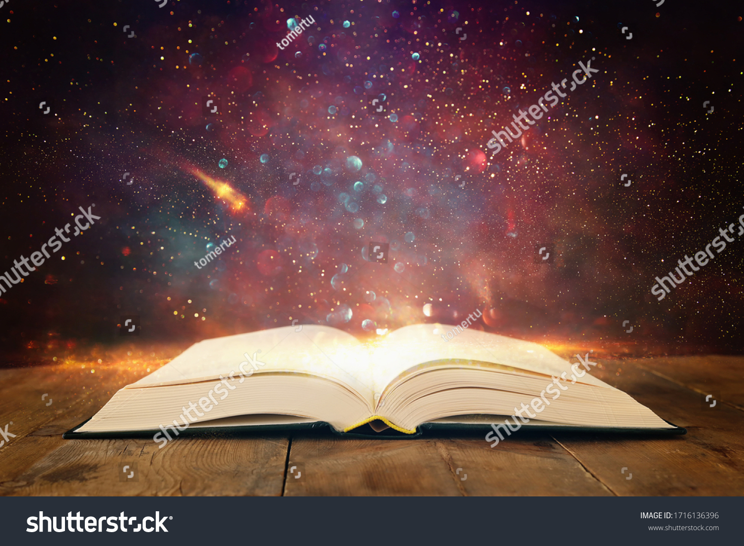 image of open antique book on wooden table with glitter overlay #1716136396
