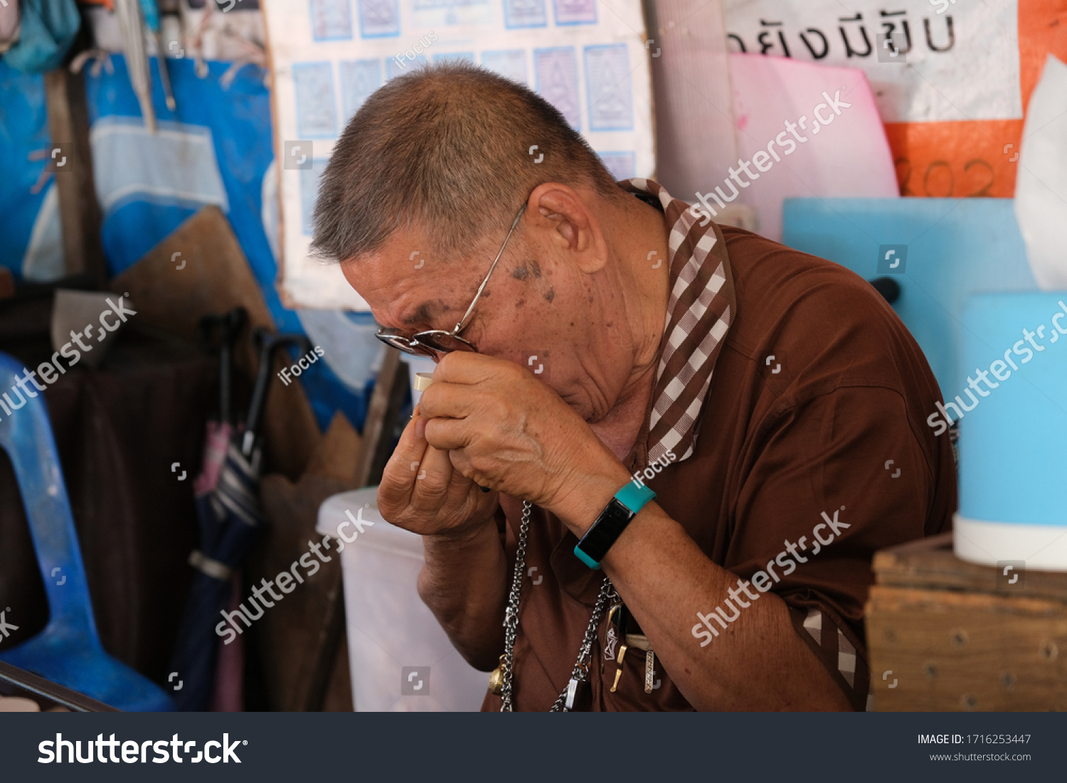 BANGKOK, THAILAND - FEBRUARY 15, 2020: An unidentified man uses a magnifier to look at an amulet on February 15, 2020, in Bangkok, Thailand.