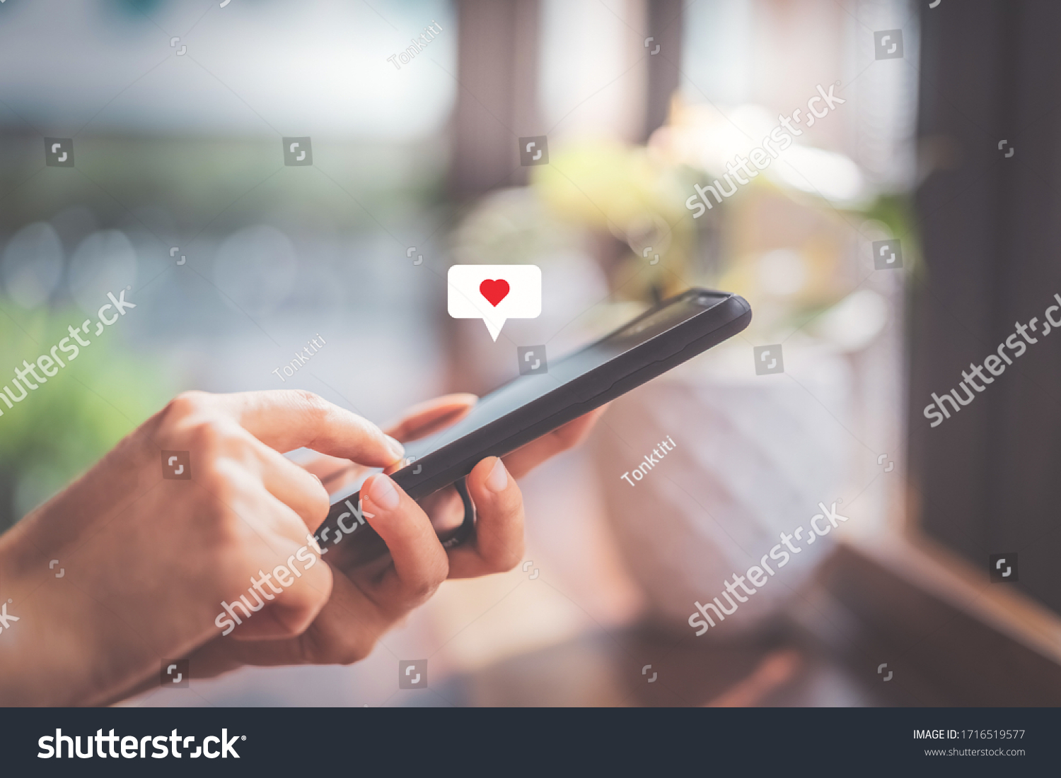 Woman hand using smartphone with heart icon at coffee shop background. Technology business and social lifestyle concept. Vintage tone filter effect color style. #1716519577