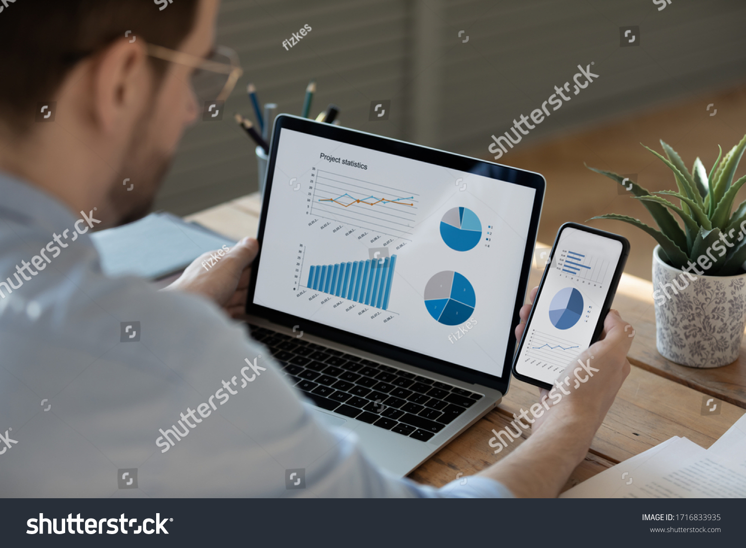 Close up businessman working with statistics, looking at laptop and phone screens with graphs and diagrams, synchronizing electronic devices, checking financial report presentation, sitting at desk #1716833935