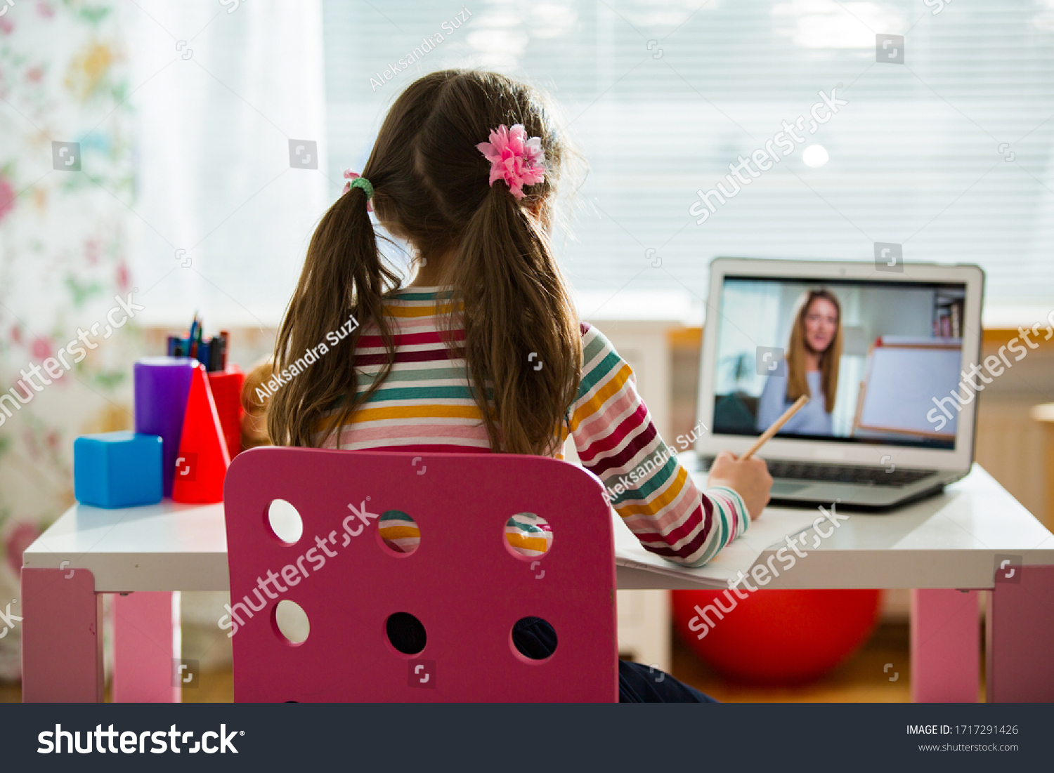 Young female distance teacher having video conference call with pupil using webcam. Online education and e-learning concept. Home quarantine distance learning and working from home. #1717291426