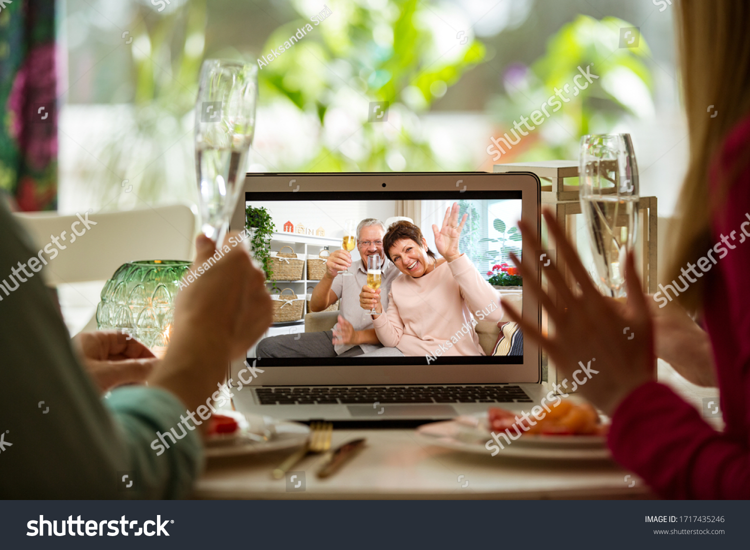 Man and woman sitting at the dining table, having dinner, drinking Champagne and having video call with senior parents on laptop. Staying home, quarantine and social distancing celebration of event.  #1717435246