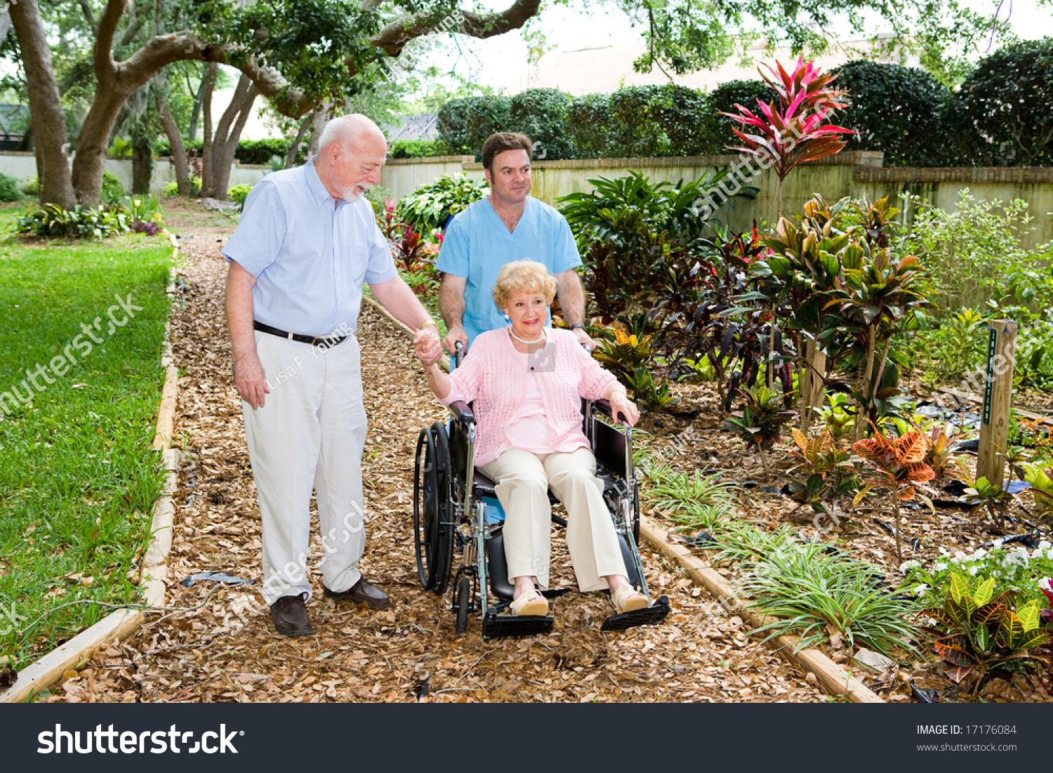senior woman in a wheelchair being walked through the nursing home garden by an orderly and - The Garden Nursing Home