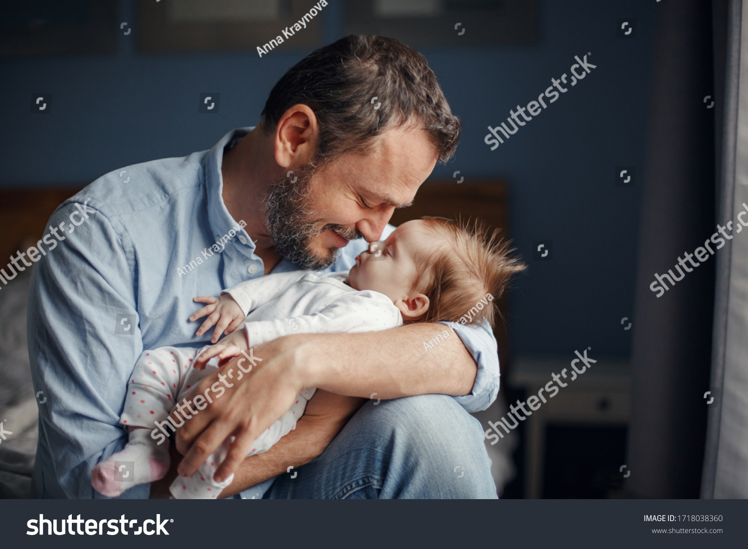 Middle age Caucasian father kissing sleeping newborn baby girl. Parent holding rocking child daughter son in hands. Authentic lifestyle parenting fatherhood moment. Single dad family home life. #1718038360