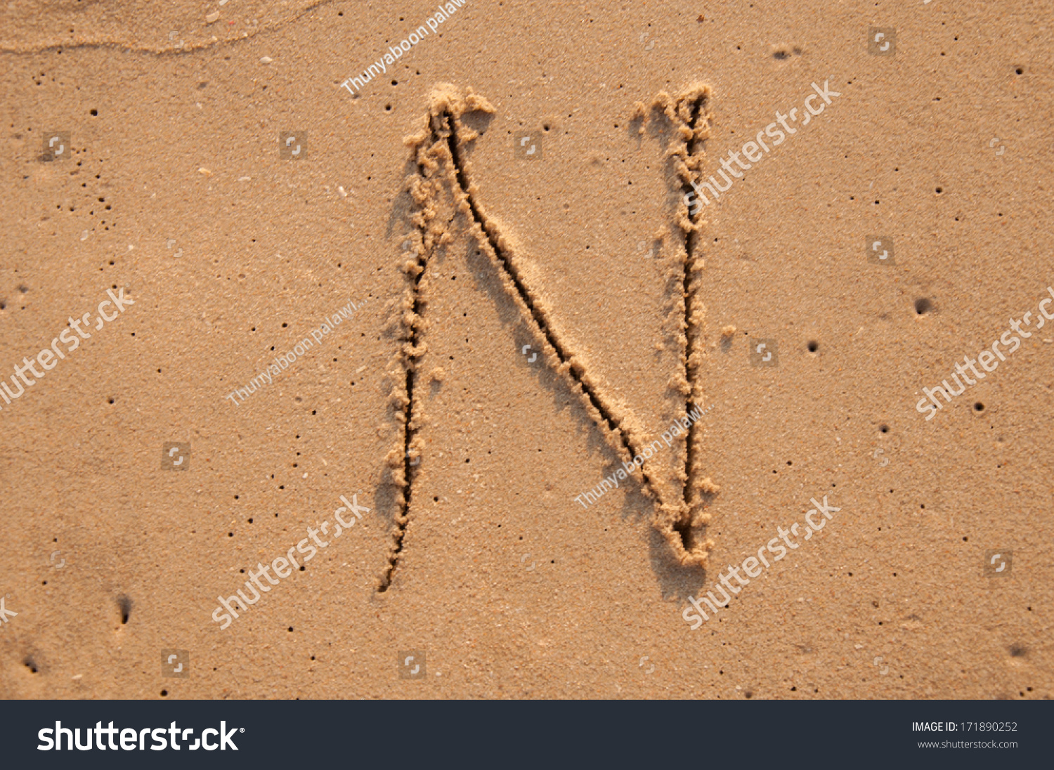 N text written in the sandy on the beach #171890252