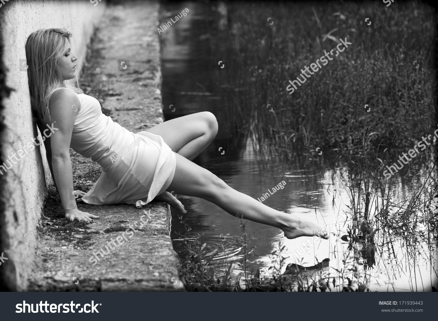 https://image.shutterstock.com/z/stock-photo-blonde-woman-wearing-a-white-dress-is-sitting-on-the-edge-of-a-pond-she-is-barefoot-she-tries-171939443.jpg