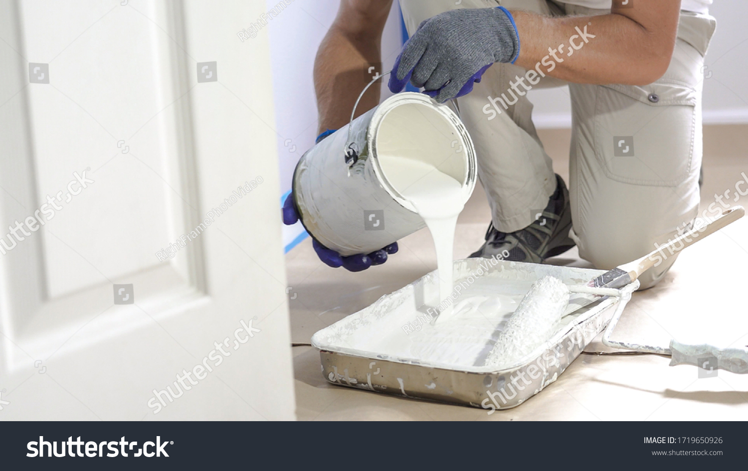 Man pours paint into the tray and dips roller. Professional interior construction worker pouring white color paint to tray. #1719650926