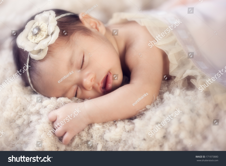 Portrait of a beautiful newborn mixed race hispanic caucasian baby girl sleeping wearing a headband laying
