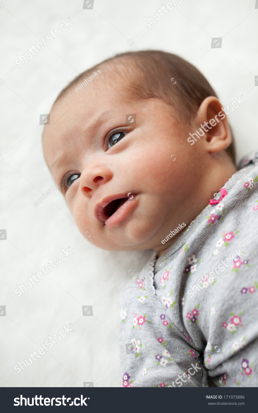 Newborn mixed race hispanic caucasian baby girl laying on a white blanket looking away