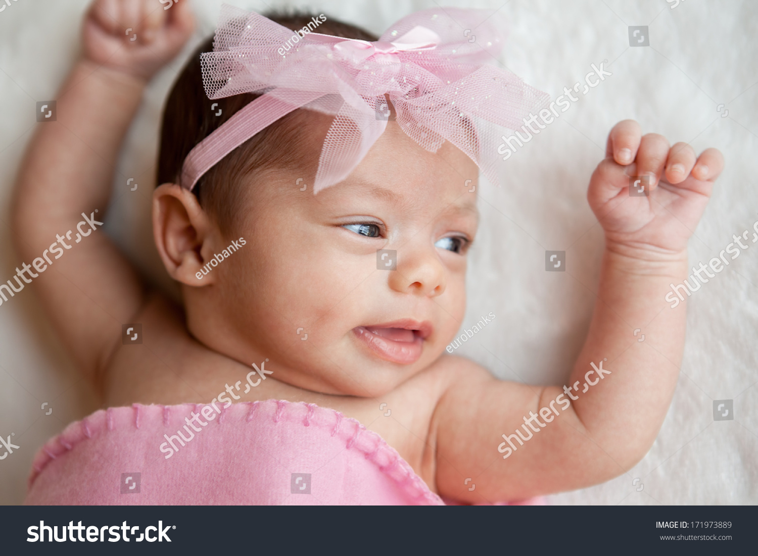Happy newborn mixed race hispanic caucasian baby girl wearing pink bow smiling with arms in the