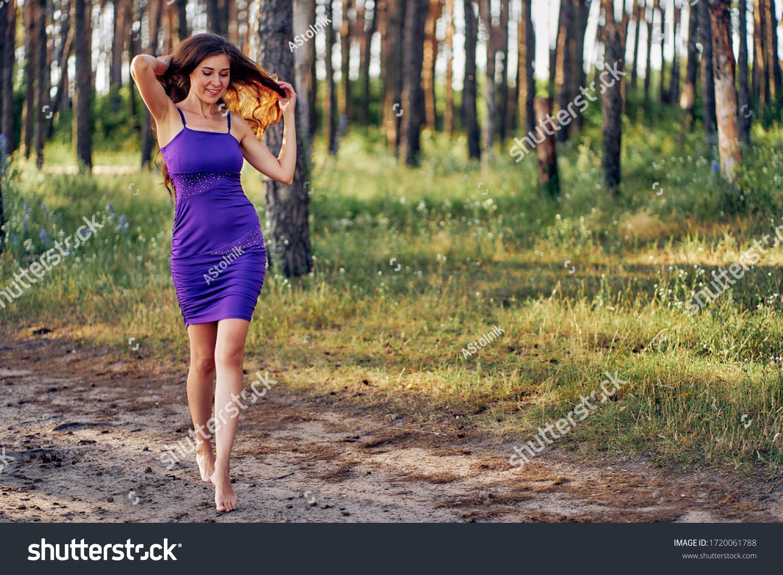 https://image.shutterstock.com/z/stock-photo-beautiful-woman-walks-barefoot-in-a-short-blue-dress-walks-in-the-park-at-sunset-1720061788.jpg
