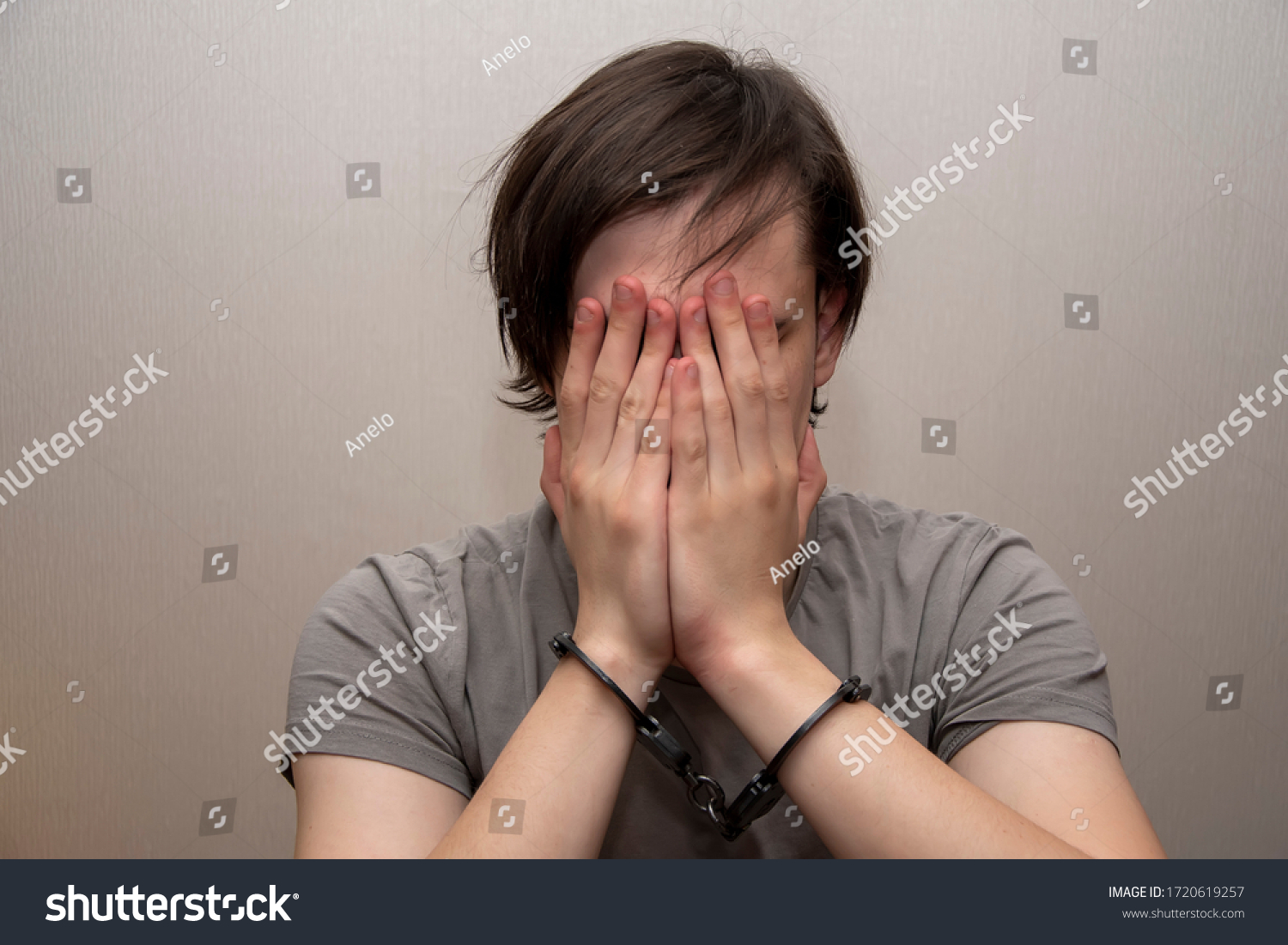 Portrait of a teenager in handcuffs covering his face with his hands on a gray background, medium plan. Juvenile delinquent, criminal liability of minors. Members of youth criminal groups and gangs. #1720619257