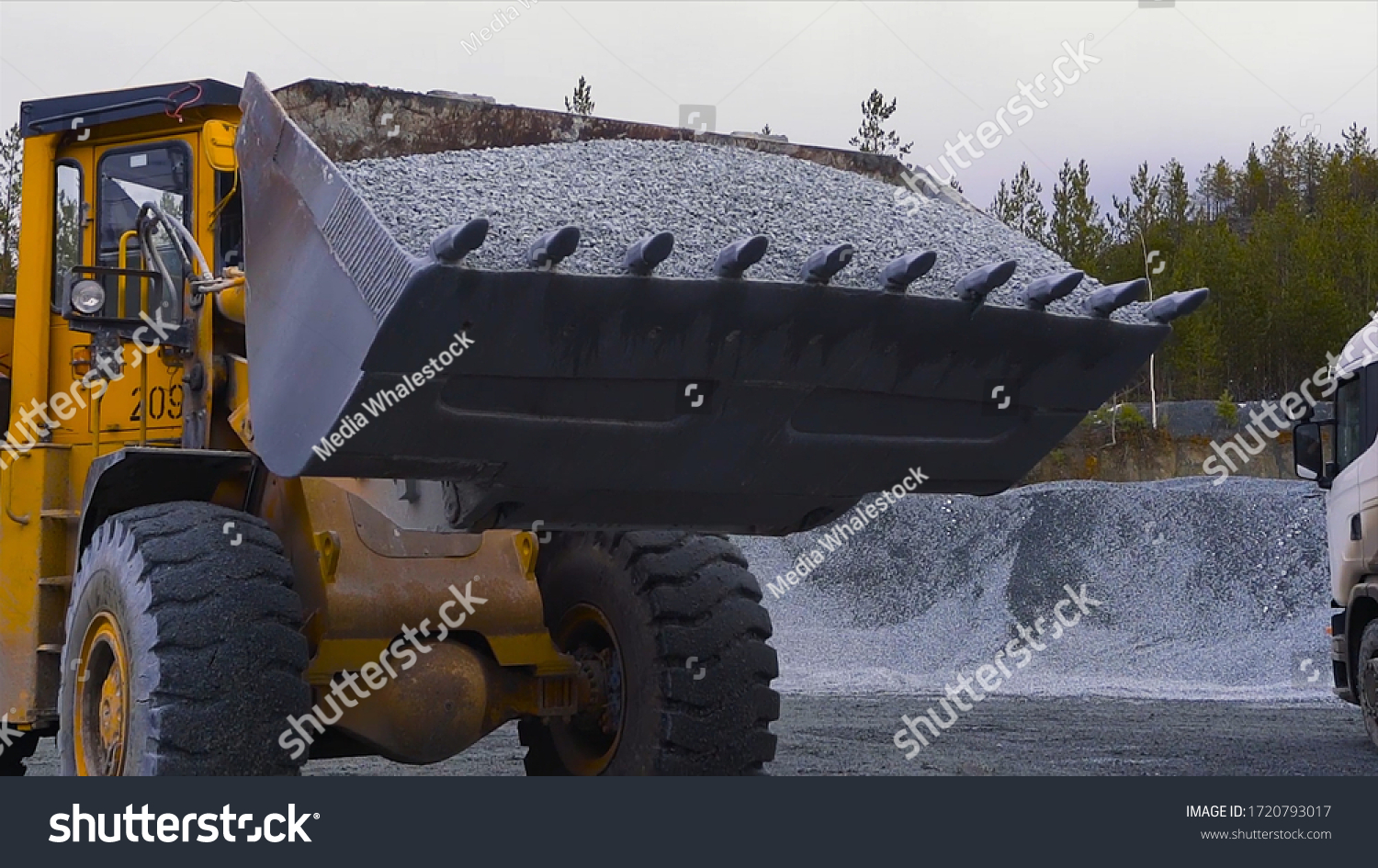 Tractor moves rubble to truck. Stock footage. Excavator-loader rakes rubble from pile at construction site and loads dump truck. Clearing site or mining rubble with heavy transport #1720793017