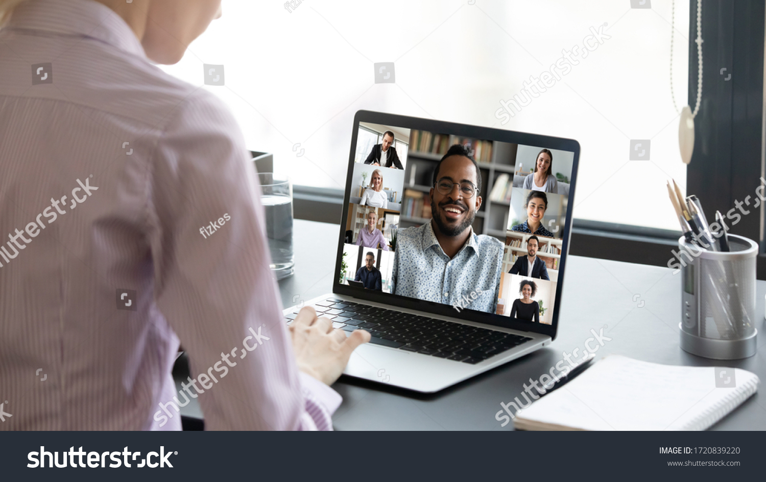 Close up of woman worker sit at desk talk speak on video call with multiracial colleagues or friends, female employee have online briefing with international team, engaged webcam conference at home #1720839220