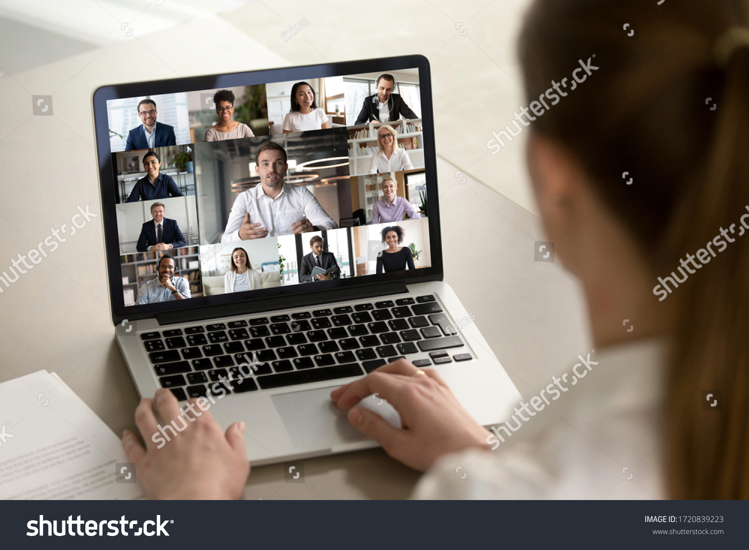 Back view of female employee engaged in web team meeting briefing using laptop at home, have webcam conference, woman worker talk on video call with diverse multiracial colleagues on computer #1720839223