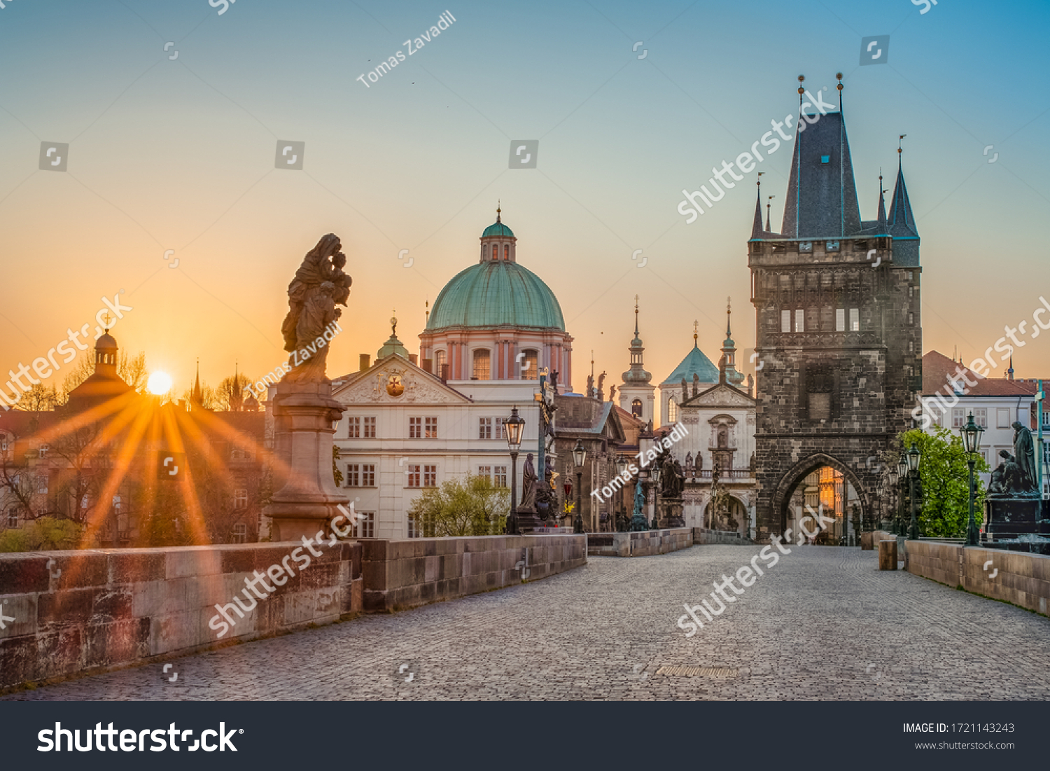 Sun rays filling the scene with colors during sunrise on empty deserted Charles bridge in Prague, Czech Republic  #1721143243