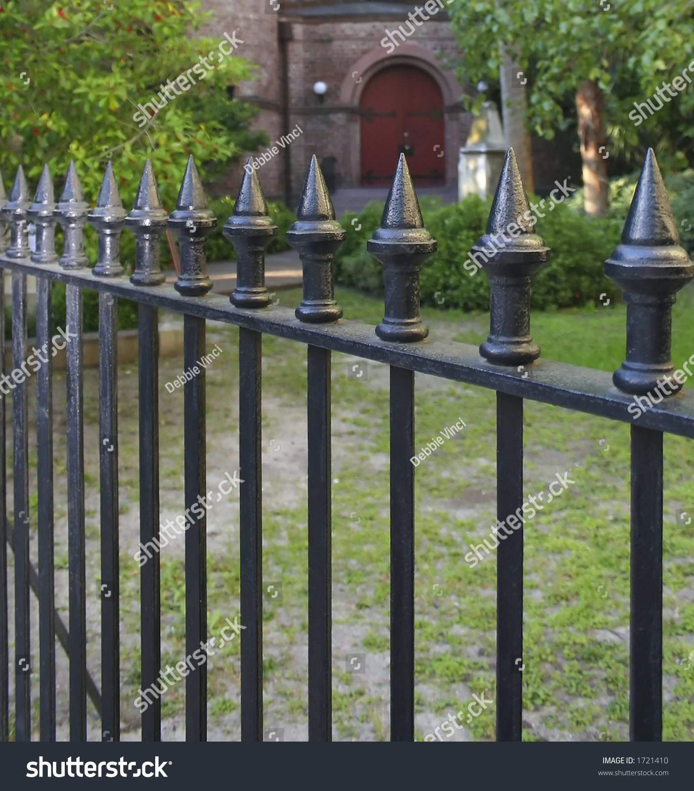 black metal picket fence front brick stock photo