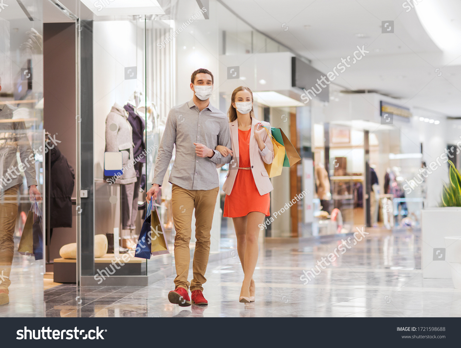 sale, consumerism and pandemic concept - happy young couple wearing face protective medical mask for protection from virus disease with shopping bags walking in mall #1721598688