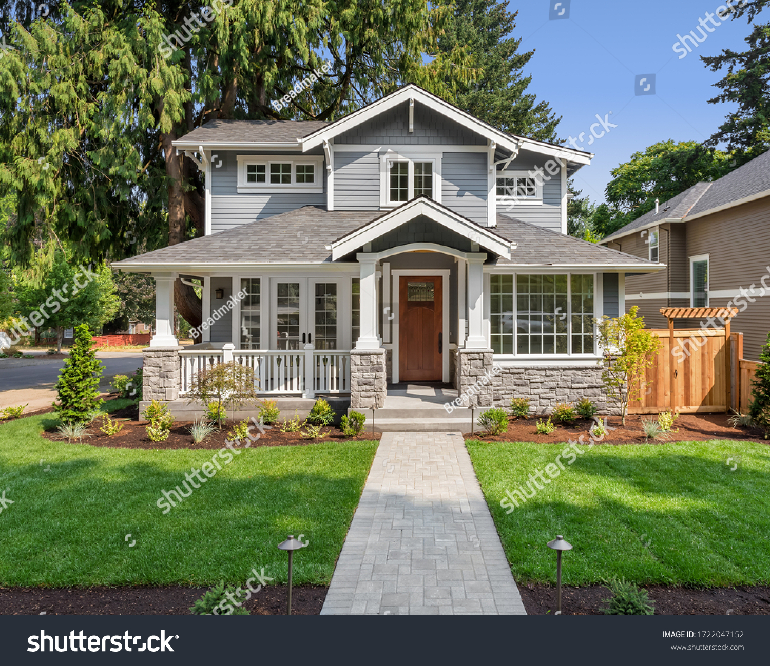 Beautiful new home exterior with covered porch and green grass on bright sunny day with blue sky #1722047152