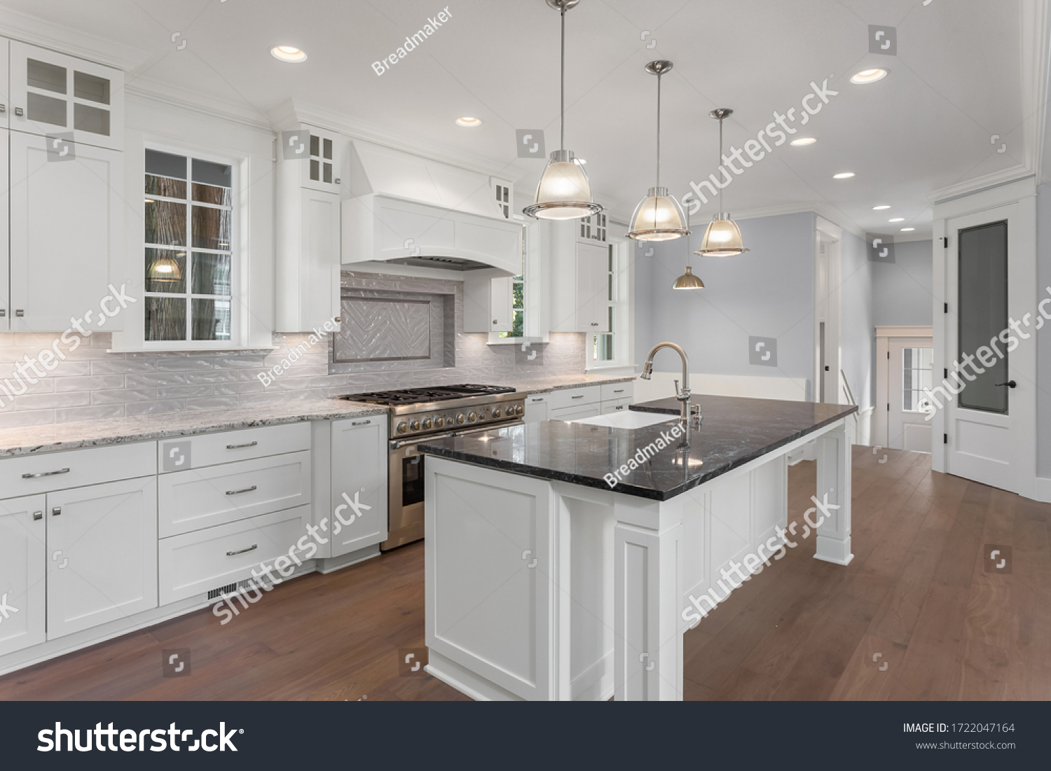 Beautiful kitchen in new luxury home with large island, hardwood floor, and pendant lights #1722047164