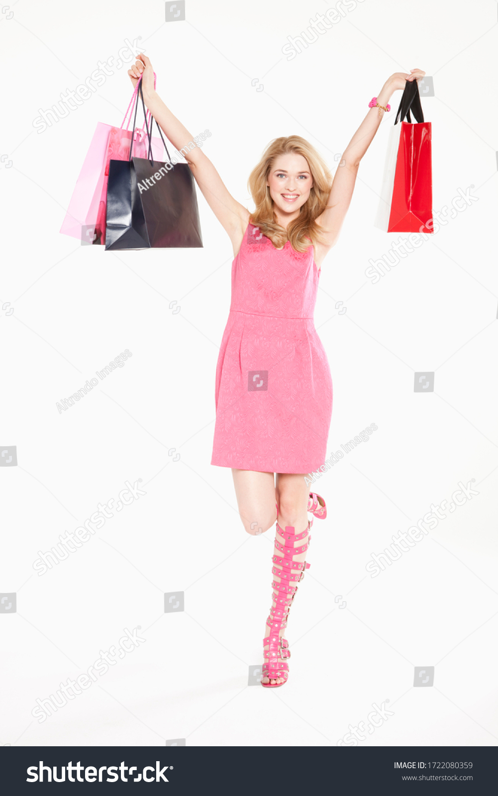 Young woman in pink dress and heels holding shopping bags, portrait #1722080359
