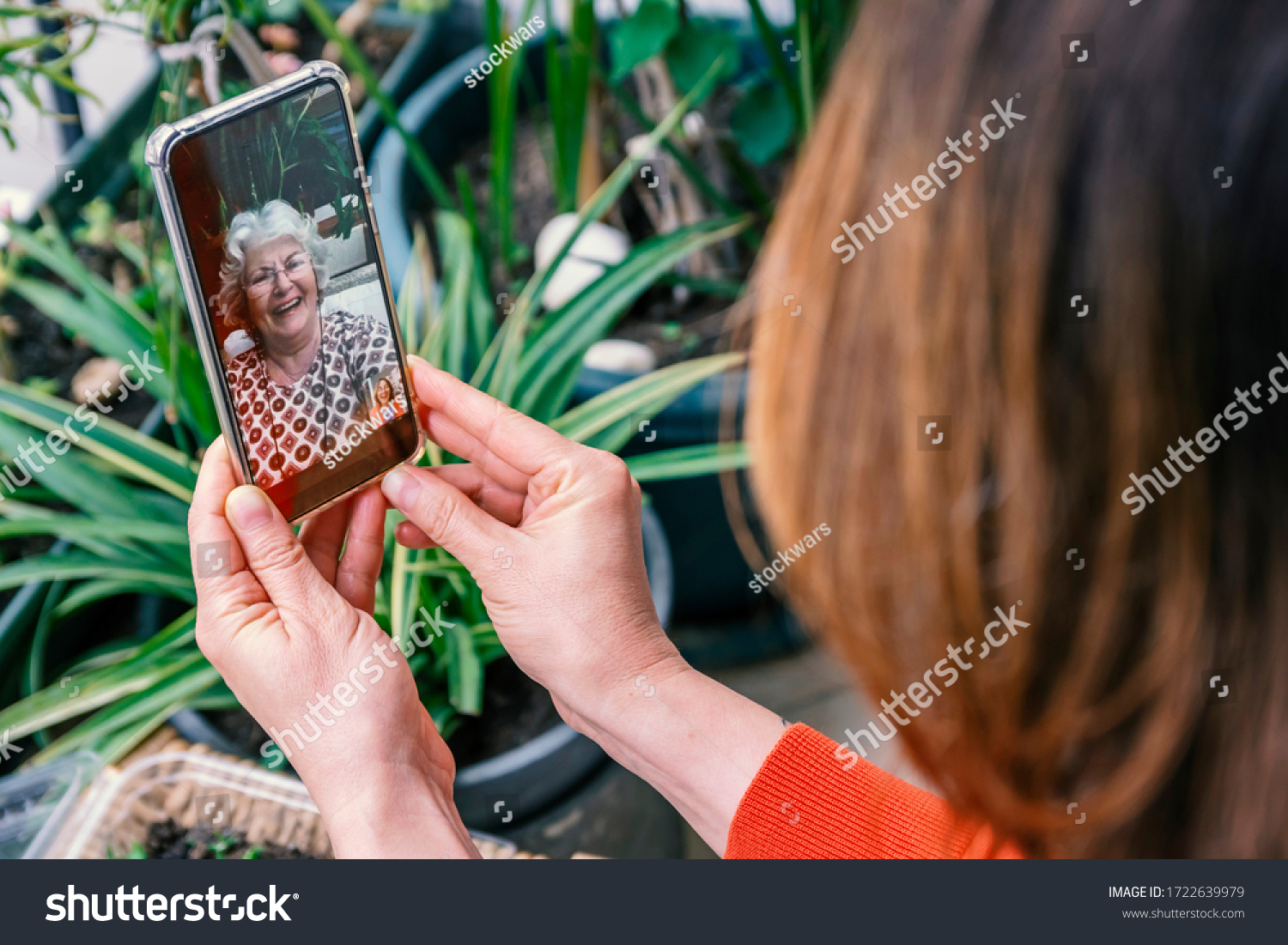 Mother's day lockdown concept: Mother and child laughing during online video call, celebrating this special day. Woman with white hair and glasses smiles into camera. Green leaves in background #1722639979